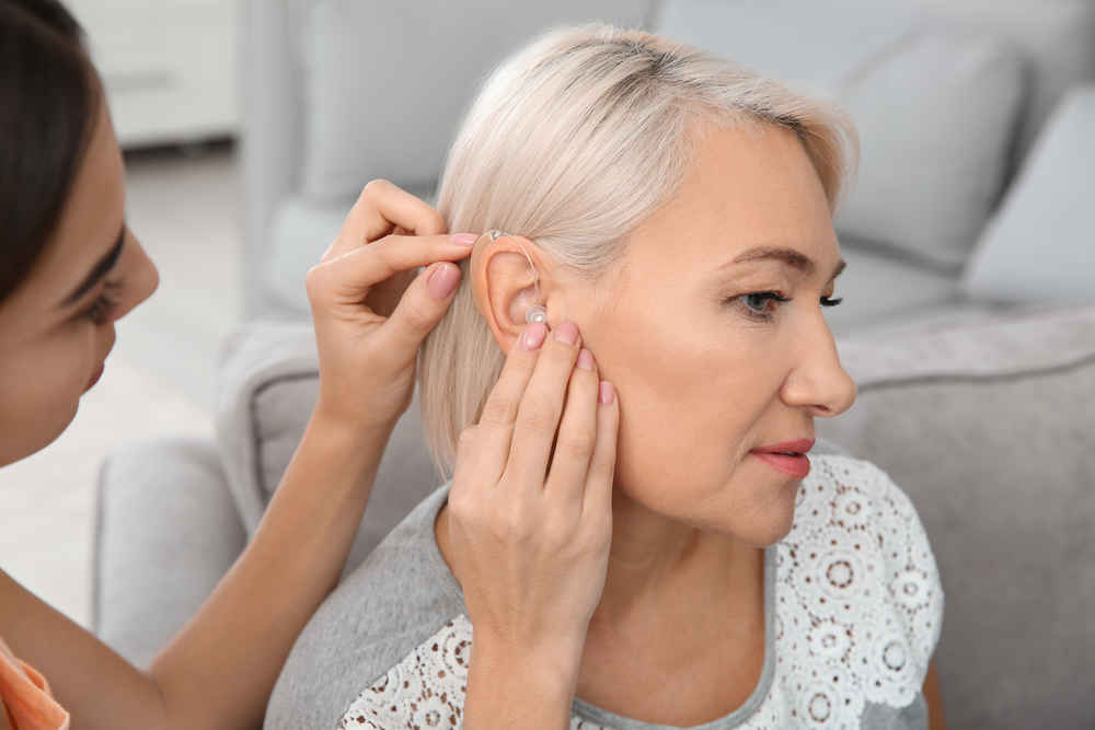 Audiologist fixing hearing aid